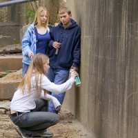 Three teenagers spraying graffiti on wall